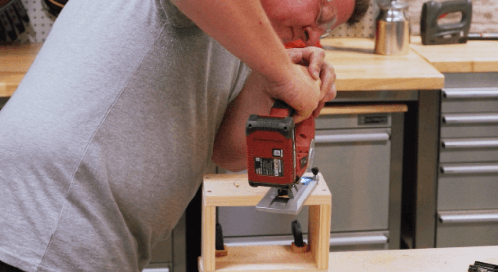 Man cutting circle with red cordless jigsaw