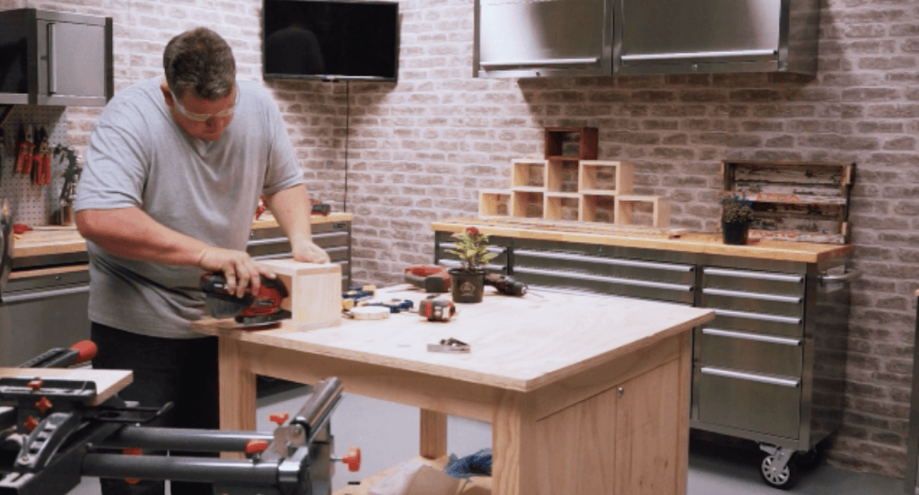 man using red cordless detail sander