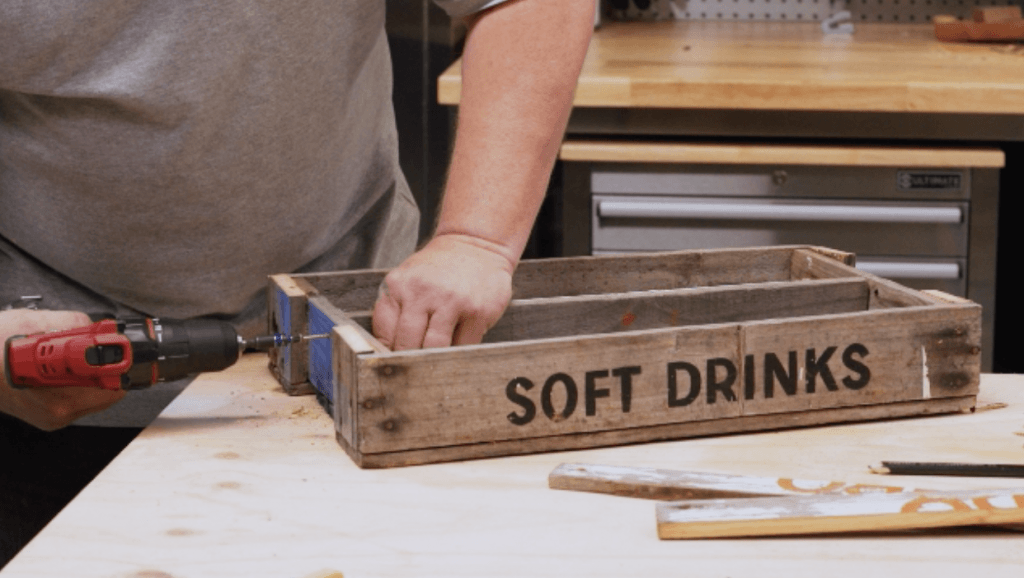 Drilling holes into wooden drinks crate